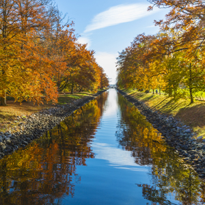 A canal in the fall and trees with colourful leaves.