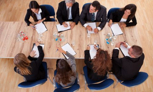Overhead view of a group of professional business people in a meeting seated around a wooden table with their notepads.