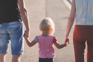 Child in the middle holding hands with parents going for a walk.