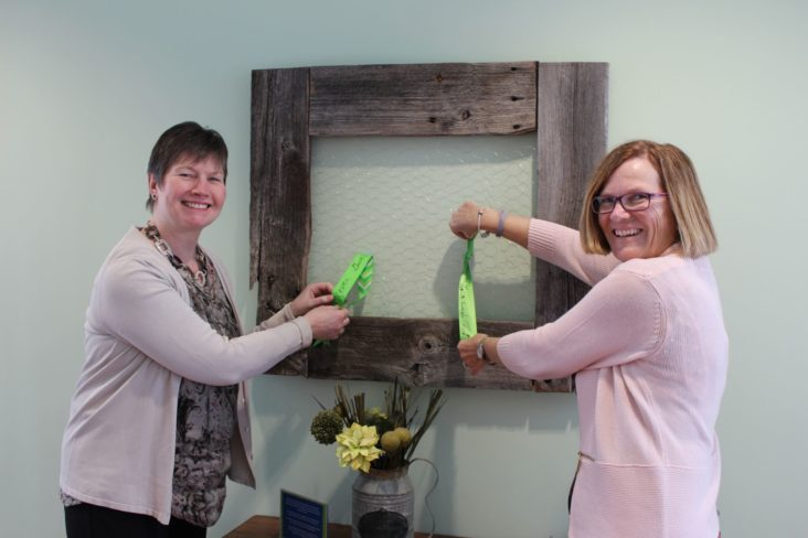 Kelly Seymour and Liz McKeeman, New Path Youth and Family Services. Looping ribbons through a barn board frame with inspirational messages.