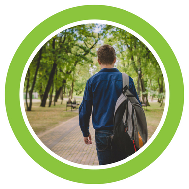 Picture of a male teen walking down a path surrounded by trees
